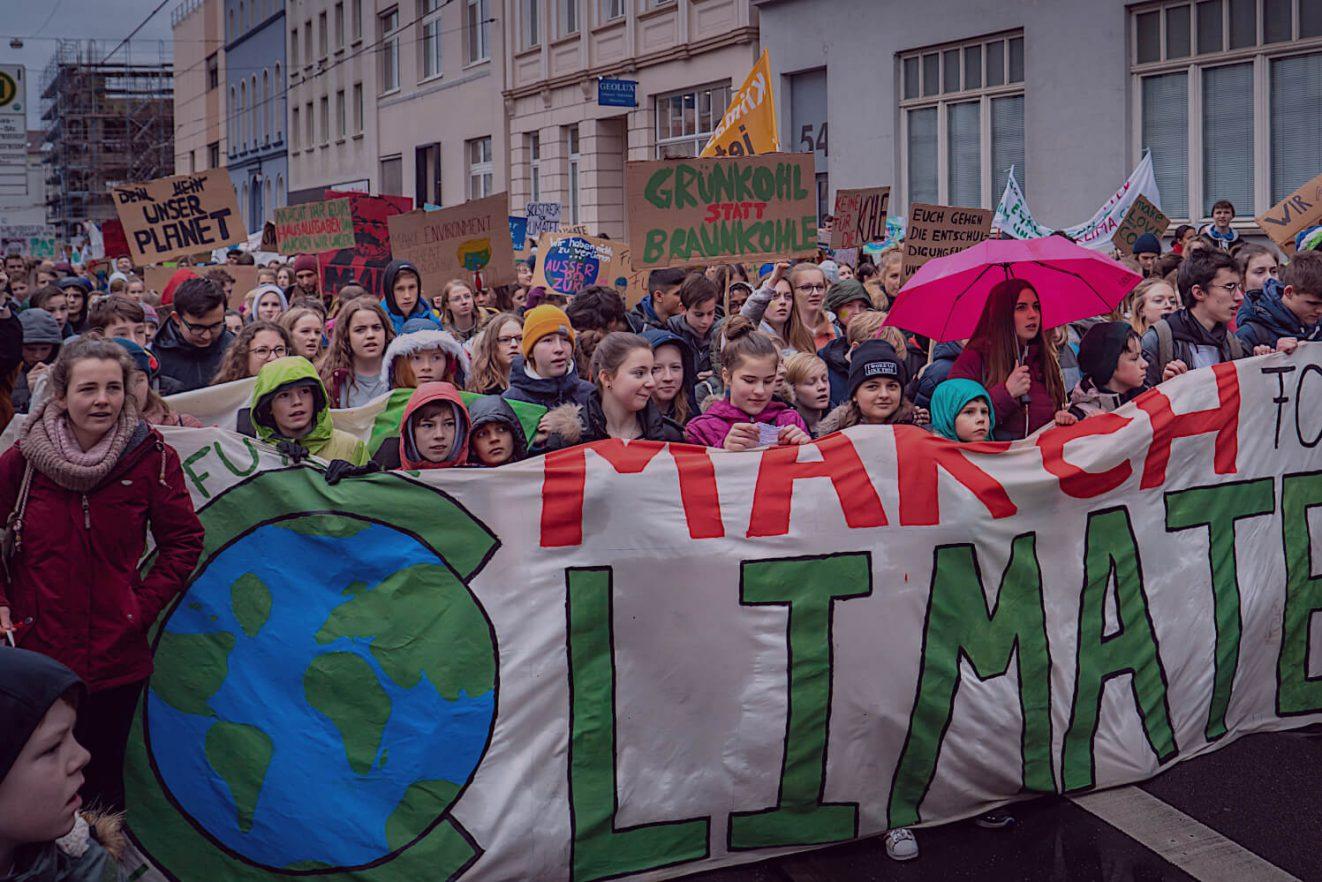 Das Bild zeigt Mitglieder der Generation Z, die für das Klima protestieren. In der Y Politik-Podcast-Folge zum Bild geht es um den Generationenkonflikt der Generation Z mit den Babyboomern.