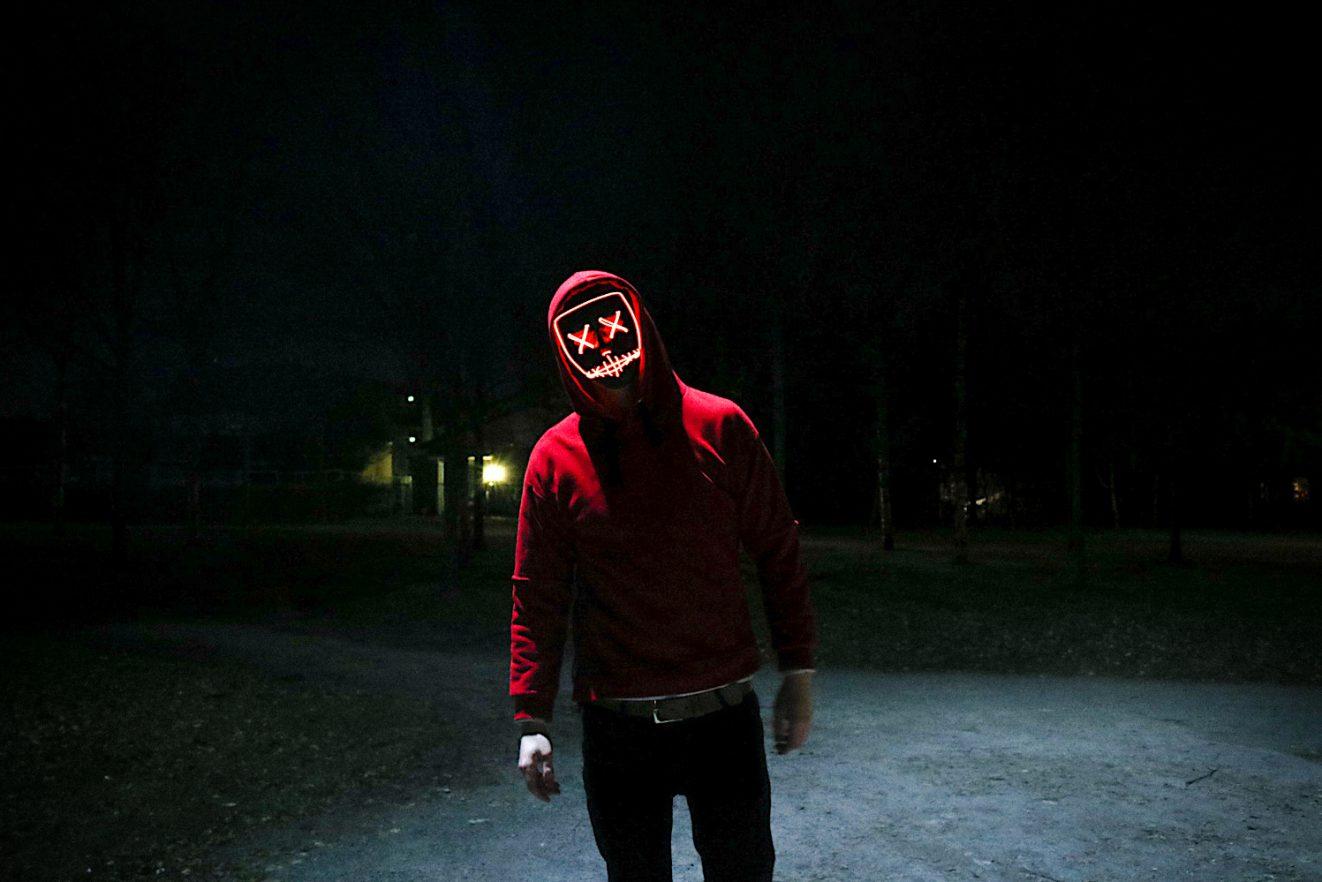 Das Foto zeigt einen Mann im roten Sweater beio Nacht. Statt dem Gesicht sieht man einen bösen Smiley. Das Foto bebildert die Folge 32 des Y Politik-Podcasts zur Frage, was man gegen den Hass tun kann.