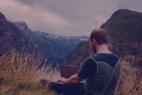 Das Foto zeigt einen Mann, der in der Natur am Laptop sitzt. Das Foto illustriert Folge 36 vom Y Politik-Podast über die Chancen der Digitalisierung für ländliche Regionen.