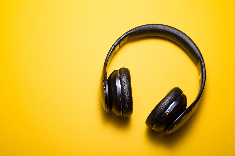 Das Foto zeigt Kopfhörer auf gelbend Grund. Das Foto illustriert einen Artikel über Politik-Podcasts für junge Menschen auf Spotify.