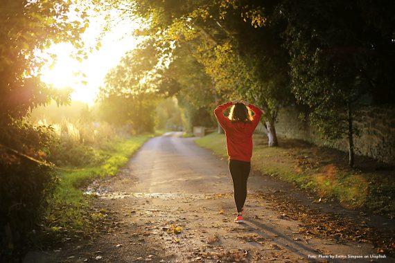Das Foto zeigt eine Frau in roter Sportkleidung wie sie durch einen Park geht. Das Foto bebildert eine Y Politik-Podcast-Folge über Arbeitszeitverkürzung.