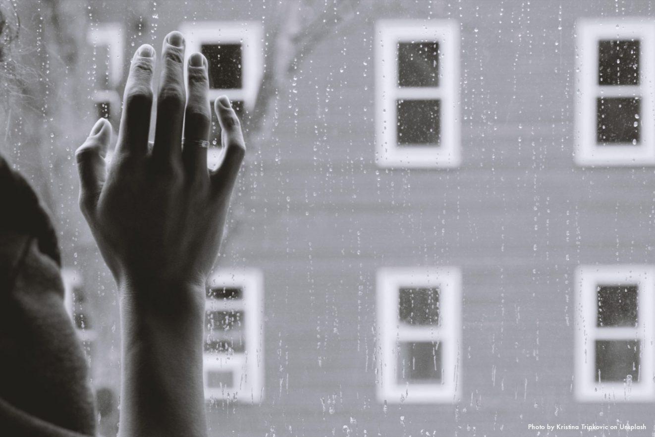 Dieses Foto zeigt die Rückhand einer Frau, die an einer verregneten Innenscheibe lehnt. Das Foto ist das Beitragsbild zur Y Politik-Podcast-Folge zum Thema warum Einsamkeit krank macht und was die Politik gegen Einsamkeit tun kann.