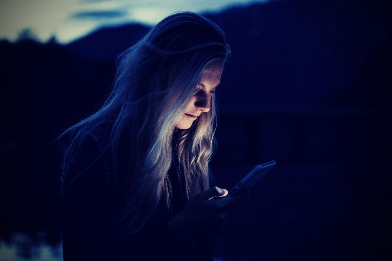 Das Bild zeigt eine blonde Frau, wie sie im Freien auf ihr Handy blickt. Das Foto illustriert einen Artikel auf Deutsch zum Thema Doomscrolling und wie man damit aufhören kann.