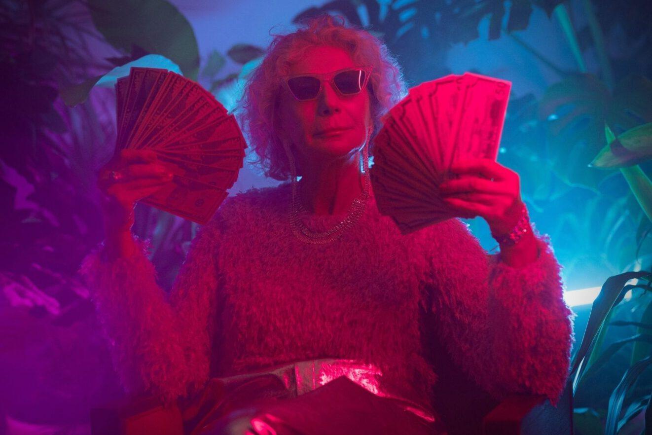 Das Foto zeigt eine ältere Frau, die Geldscheine wedelt. Es bebildert einen Artikel zum Thema: wer bezahlt die Kosten von Corona?